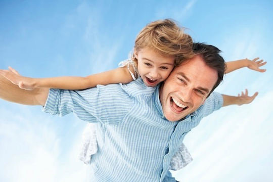 Father giving piggyback ride to daughter with arms outstretched